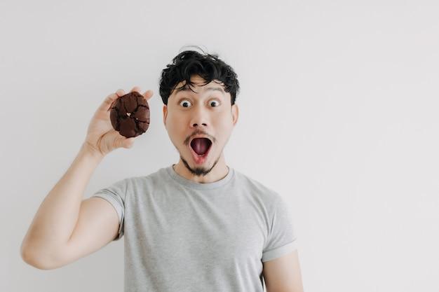 Wauw en geschokt gezicht van de man voelt zich opgewonden met het enorme chocoladekoekje