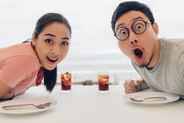 Wauw en geschokt gezicht van geliefde paar met een date in het restaurant op het strand. Premium Foto