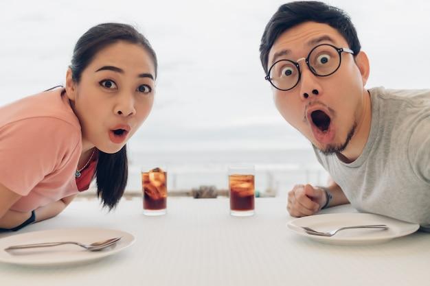 Wauw en geschokt gezicht van geliefde paar met een date in het restaurant op het strand.