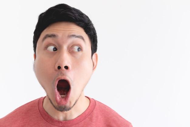 Wauw en geschokt gezicht van grappige aziatische man geïsoleerd op een witte achtergrond.