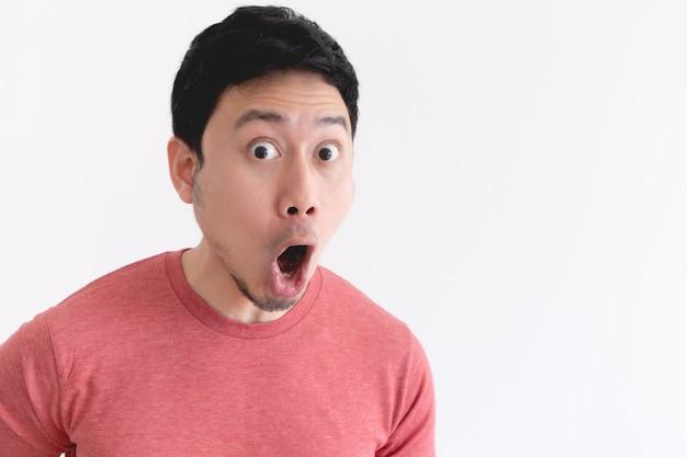 Wauw en geschokt gezicht van grappige aziatische man geïsoleerd op een witte muur.