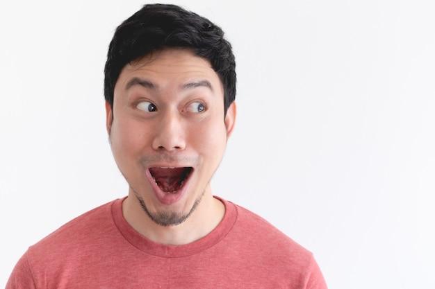 Wauw en geschokt gezicht van grappige aziatische man geïsoleerd op een witte muur