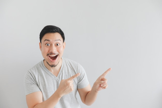 Wauw en verbaasd gezicht van de mens in grijze t-shirt met handpunt op lege ruimte.