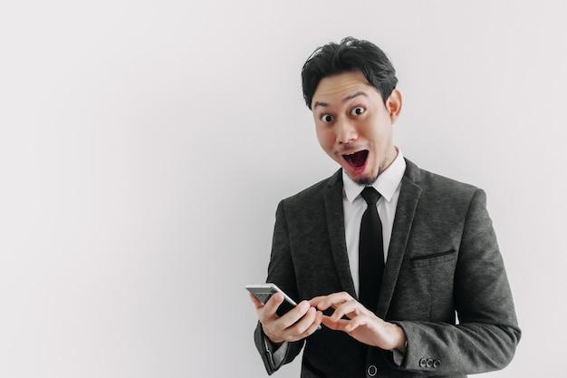Wauw en verrast gezicht van zakenman gebruikt handelsapplicatie aan de telefoon