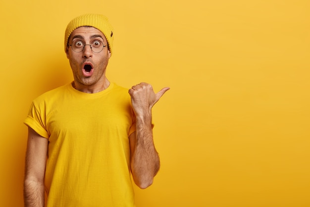 Wauw, enorme kortingsmogelijkheid. gevoelige man met angstige gezichtsuitdrukking toont onverwachte kansen, wijst met zijn duim naar de lege ruimte, draagt gele outfit. advertentie