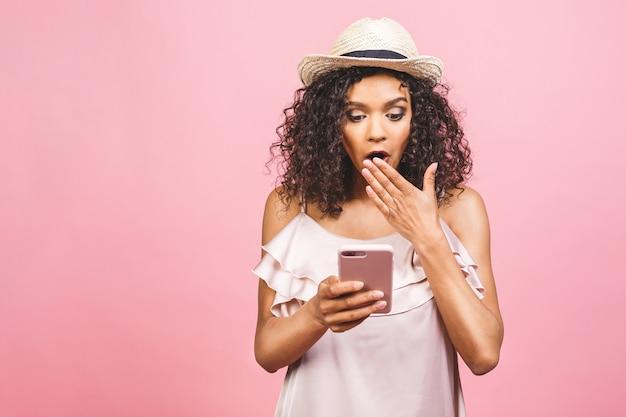 Wauw, geweldig nieuws! portret van een geschokt jong afro-amerikaans meisje dat in kleding mobiel bekijkt