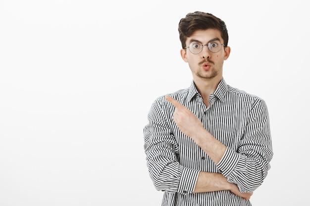 Wauw geweldig. verrast geïnteresseerde europese man met baard en snor in bril, lippen vouwen en naar de linkerbovenhoek wijzend, geïntrigeerd en nieuwsgierig, assistent vragen om dichterbij item te laten zien