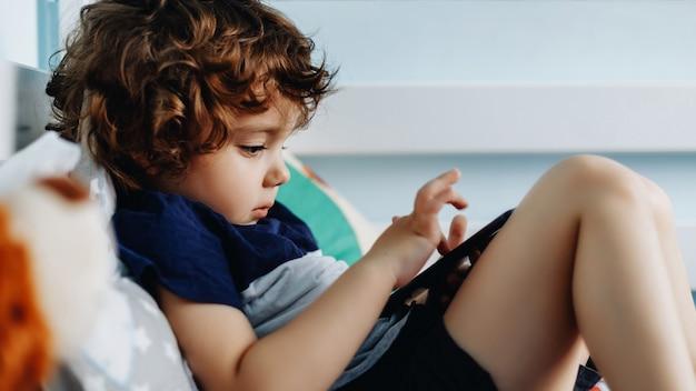 Wauw, ik vind die telefoon leuk. baby met smartphone. jongenszitting in bed en het spelen met mobiele telefoon. mijn moeder bellen. schattige kleine baby houdt mobiele telefoon in zijn handen en aandachtig kijken naar scherm.