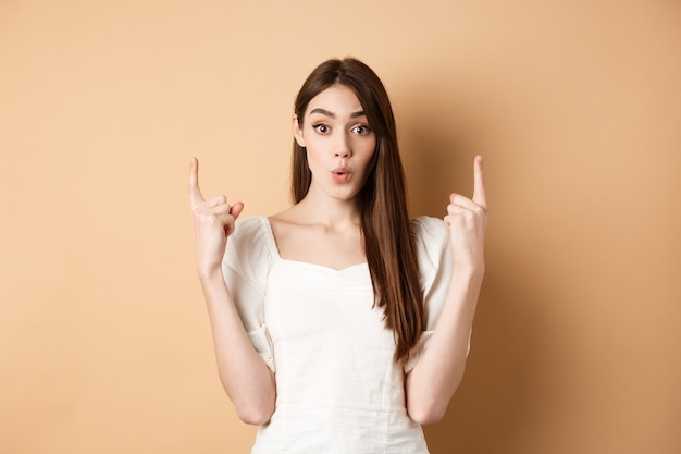 Wauw kijk. geïntrigeerde jonge vrouw die interessant aanbod toont, vingers omhoog wijst en opgewonden kijkt, staande op beige achtergrond.