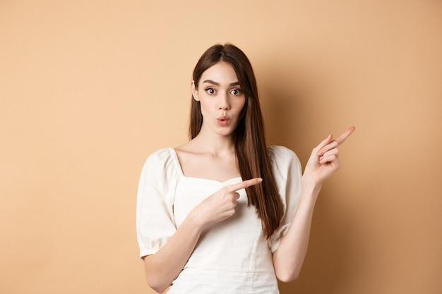Wauw kijk hier. geïmponeerde blanke vrouw in witte jurk wijzende vingers naar rechts en kijk nieuwsgierig, vraag stellen over product, beige achtergrond.