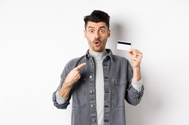 Wauw kijk hier. opgewonden man wijst naar plastic creditcard en kijkt verbaasd met geweldige deal, staande tegen een witte achtergrond.