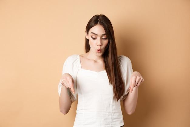 Wauw kijk. verbaasd mooi meisje dat promo-deal bekijkt, vingers naar beneden wijst en verbaasd naar adem snakt, reclame toont, beige achtergrond.
