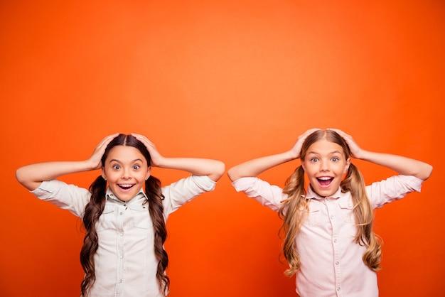 Wauw koopjes in de herfst! portret van funky gekke twee kinderen horen ongelooflijk nieuws schreeuwen omg aanraking handen hoofd dragen witte shirts outfit geïsoleerd op oranje kleur achtergrond