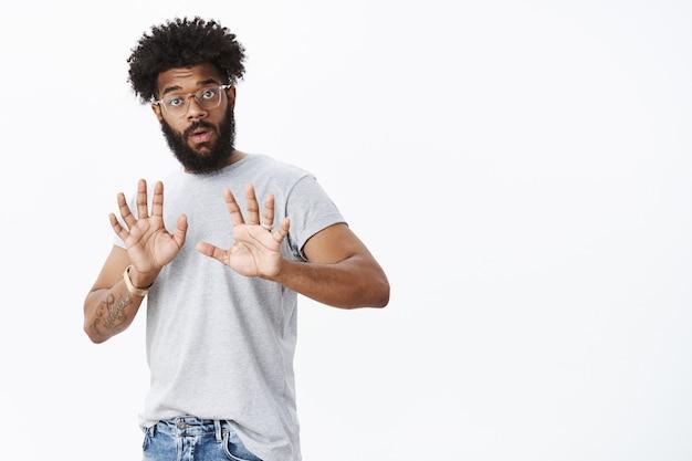 Wauw langzamer. portret van intens ontstemde en geschokte, freak-out afro-amerikaanse mannelijke vriend met krullend haar en baard die handen opheft in een kalmerend gebaar dat waarschuwing geeft en weigering geeft