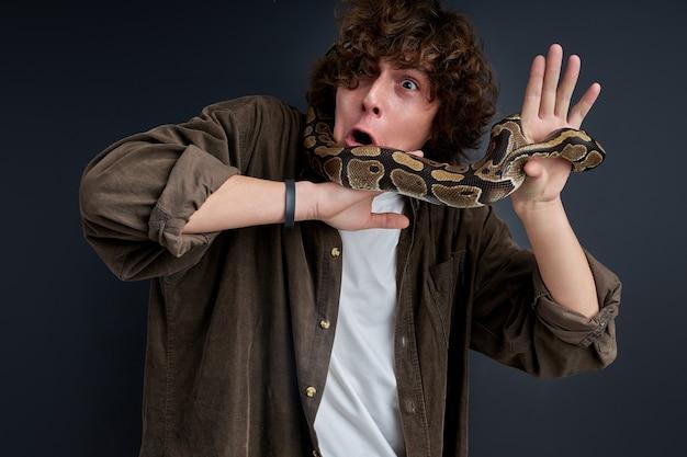 Wauw. man reageert emotioneel op slang die in shock over zijn lichaam kruipt. geïsoleerde zwarte achtergrond
