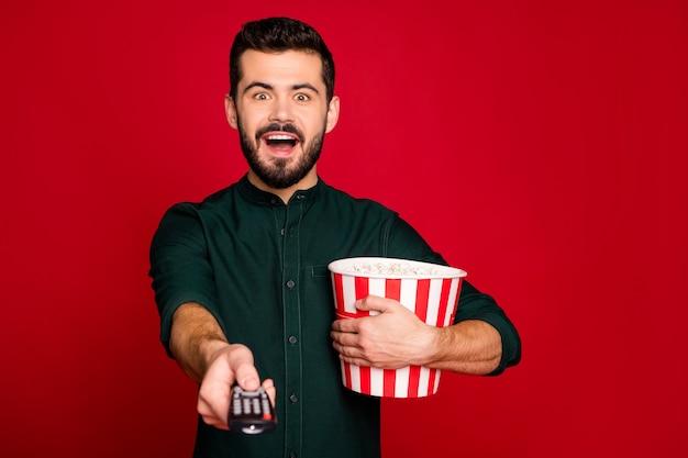 Wauw mijn favoriete film! opgewonden gekke kerel die rust heeft, tv kijken, schreeuw, houdt grote rood gestreepte popcorndoos schakelaar afstandsbediening draagt moderne kleding