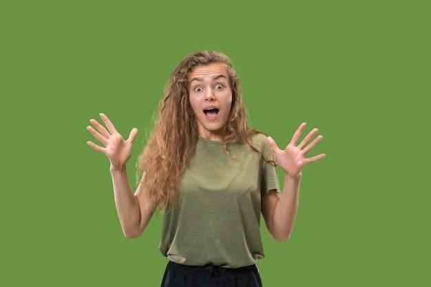 Wauw. mooi vrouwelijk half-lengte voorportret dat op groene studio achtergrondgeluid wordt geïsoleerd. jonge emotionele verrast vrouw stond met open mond.