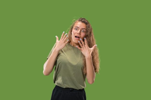 Wauw. mooi vrouwelijk half-lengte voorportret dat op groene studio wordt geïsoleerd