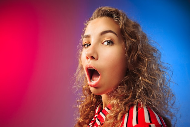Wauw. mooi vrouwelijk half-lengte voorportret op rode en blauwe studio