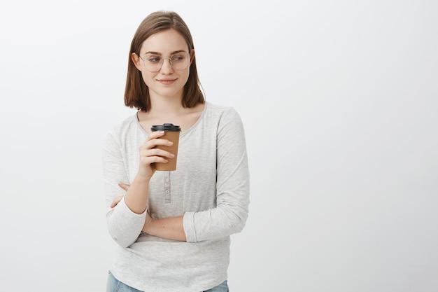 Wauw mooie kont. portret van naugty knappe enthousiaste vrouw met bruin haar in glazen grijnzend en starend naar de rechter benedenhoek koffie drinken terwijl staande in de buurt van café poseren over grijze muur