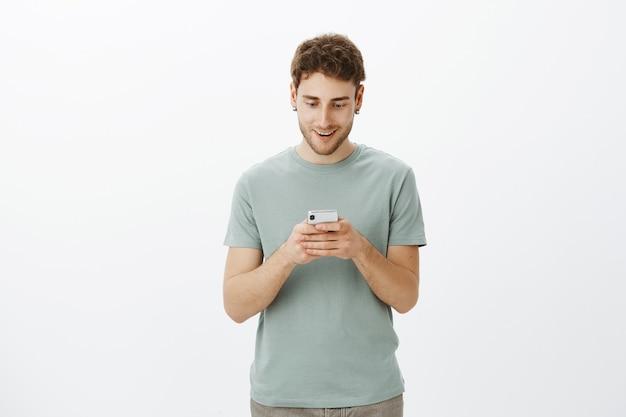 Wauw, nieuwe game is geweldig. portret van blij en tevreden gelukkig europese man in t-shirt, smartphone in handen houden en gefascineerd op zoek naar scherm