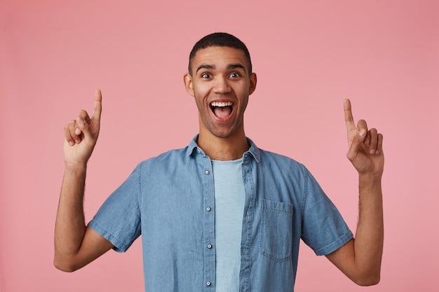 Wauw; op zoek! blij verbaasde jonge aantrekkelijke donkere man in een geruit overhemd, wijd open mond en ogen, staat op roze achtergrond wil je aandacht vestigen op de kopie ruimte boven zijn hoofd.