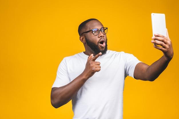 Wauw! portret van vrolijke afro-amerikaanse man op vakantie, geïsoleerd op gele muur, in vrijetijdskleding, met behulp van veb cam op zijn tablet, genieten, glimlachend.