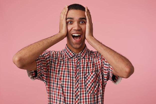 Wauw! socked jonge aantrekkelijke donkere man won een auto, kijkt naar de camera met wijd open mond en ogen, staat op een roze achtergrond en houdt zijn hoofd vast, draagt een geruit overhemd.