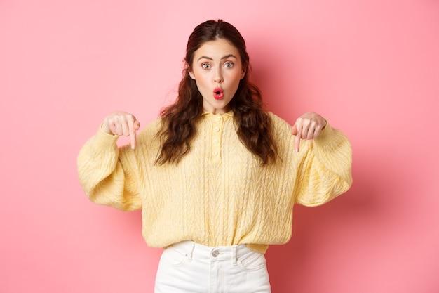 Wauw super cool opgewonden brunette meisje wijzende vingers naar beneden hijgend vroeg zich af met de richting die aangeeft op het onderste logo dat over de roze muur staat