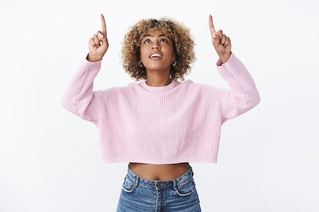 Wauw wat is dat. portret van nieuwsgierige en stijlvolle aantrekkelijke jonge 20s vrouwelijke afro-amerikaanse student met eerlijk afro kapsel kijken en omhoog wijzend met geopende mond, geïnteresseerd en geïntrigeerd