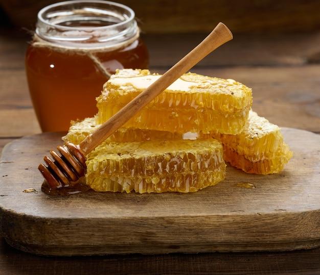 Wax honingraat met honing op een houten bord, achter een pot honing, close-up