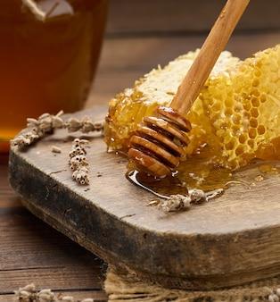 Wax honingraat met honing op een houten plank, achter een pot honing