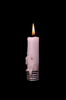 Wax kaars in gloeilamp. kaars op gloeilamp. hernieuwbare energieconcept. alternatief licht.