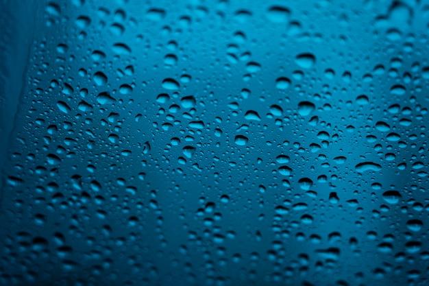 Wazig beeld van druppels regen op spiegel met gebouwen en weg achtergrond