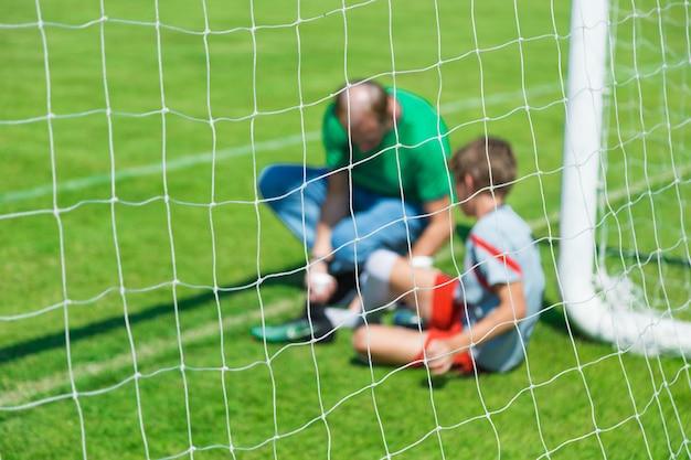Wazig beeld van een jonge gewonde mannelijke voetbal of voetbal speler die wordt behandeld