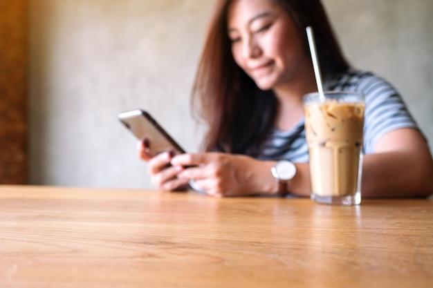 Wazig beeld van een mooie aziatische vrouw die een mobiele telefoon vasthoudt, gebruikt en bekijkt