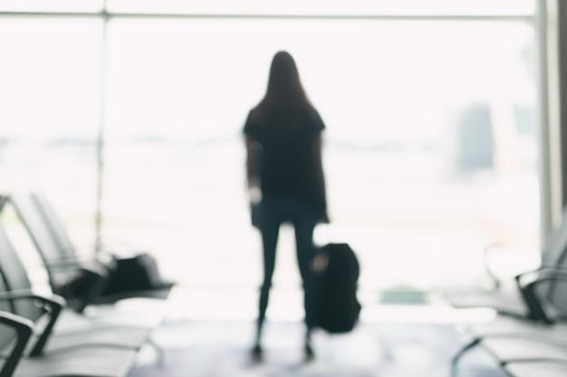 Wazig beeld van een vrouwelijke reiziger met rugzak op de luchthaven