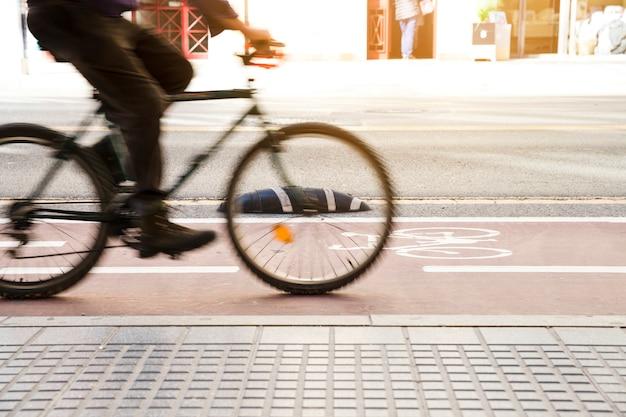 Wazig beweging van fietser rijden op de fiets rijstrook in de buurt van de stoep