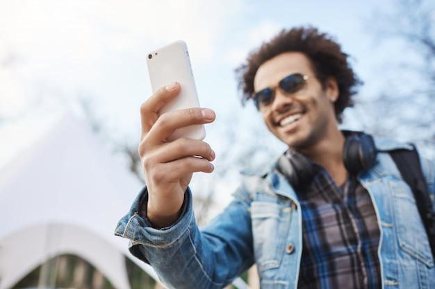Wazig buiten portret van opgewonden donkere man met afro kapsel en briste, denim kleding en bril dragen tijdens het nemen van selfie op smartphone in park, glimlachend naar gadget.