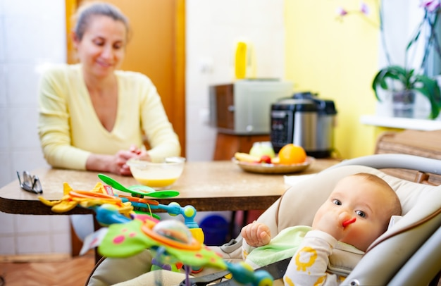 Wazig charmante lachende moeder zit aan de tafel en verheugt zich op haar kleine vrolijke pasgeboren babymeisje