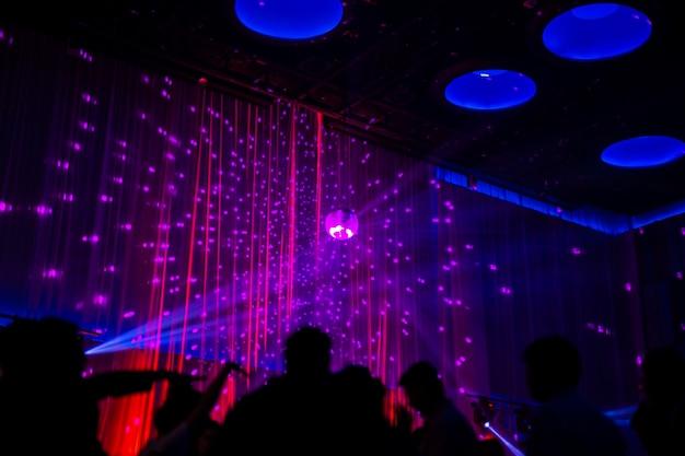 Wazig concept nachtscène in concert feest met silhoette publiek.