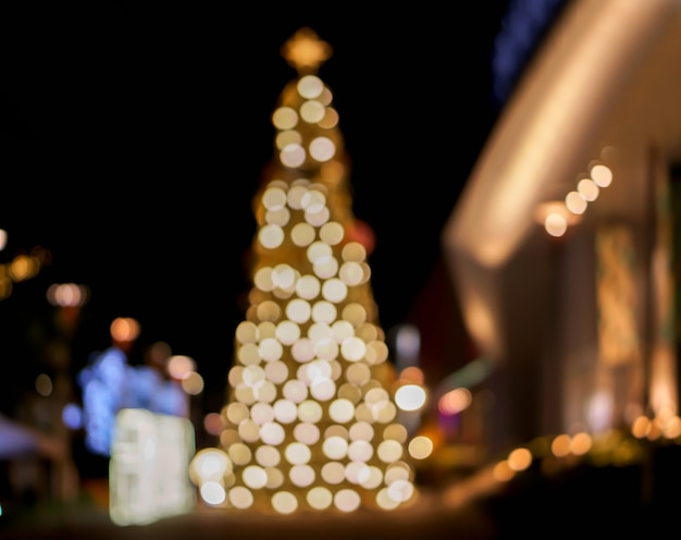 Wazig en bokeh weergave van kerstboom en versier led-verlichting voorkant van winkelcentrum op kerstnacht in stedelijke stad.
