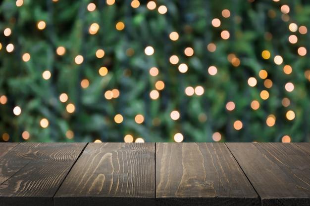 Wazig gouden slinger op kerstboom als achtergrond en houten tafelblad als voorgrond. kerst abstract. afbeelding voor weergave of montage van uw kerstproducten. kopieer ruimte.