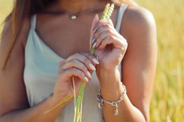 Wazig handen close-up, vrouw met mooie manicure, zilveren jurk, achtergrond van een veld