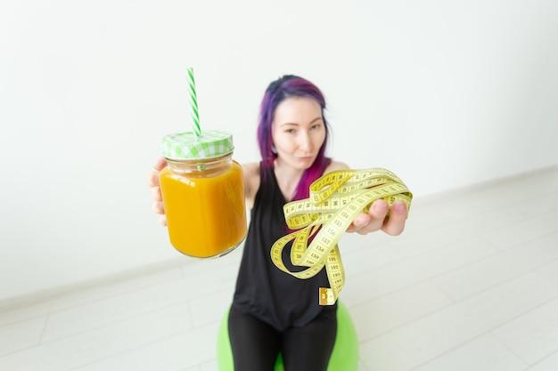 Wazig jong hipstermeisje met gekleurd haar dat een bananeneiwit-smoothie en een meetlint houdt