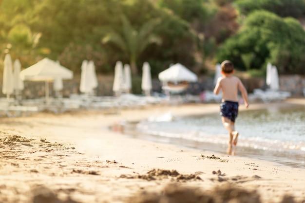 Wazig jongetje spelen, rennen op het lege privéstrand op zomervakantie. kinderen in de natuur met zee, tropische planten. gelukkige jonge geitjes op vakanties aan zee die in het water rennen, cyprus-eiland Premium Foto