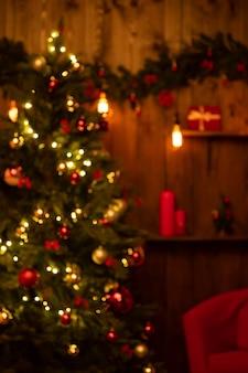 Wazig kerstboom met een slinger op de achtergrond van een houten muur