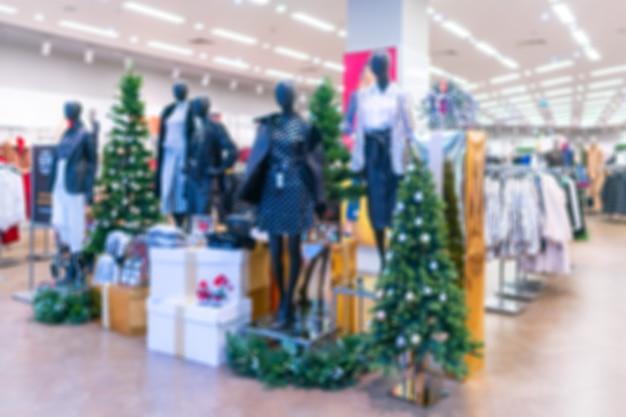 Wazig kerstmis achtergrond in een dameskledingwinkel. kerstboom in de winkel.