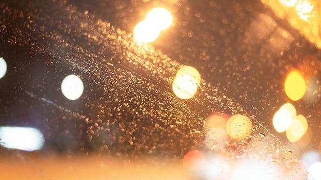 Wazig oppervlak met regendruppels en verlichting.