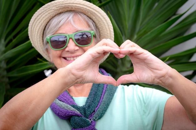 Wazig portret van een witharige lachende oudere vrouw met strohoed en groene bril die een hart vormt met haar handen. tropische planten op de achtergrond